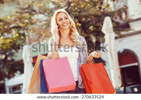 Young blond woman with shopping bags using mobile phone - stock photo