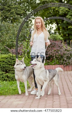 Young blond woman with two dogs Husky on dog-leads walks in summer park.