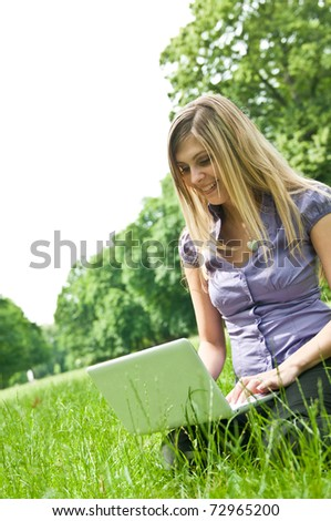 Young blond woman working with netbook outdoors in park on grass - stock photo