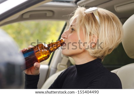 Young blond women driver drinking alcohol from a bottle and driving the car with a smile of enjoyment on her face as she poses a threat to other road users - stock photo