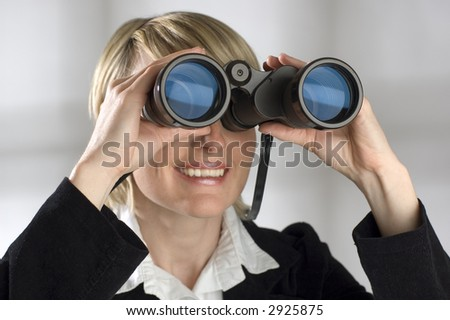 young blond women looking through binocular - business concept - stock photo