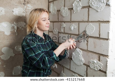 young blond worker woman worker working in room with a painter spatula and smiling