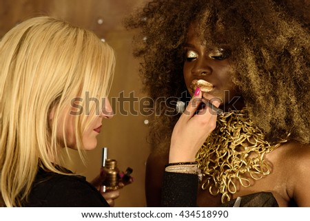 Young blonde artist painting gold lips with tassel, fashion African or Black American model wearing bright makeup and accessories - stock photo