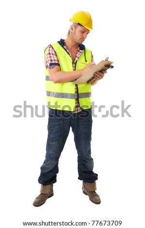 young blonde attractive builder, worker, wears yellow hardhat and hi-vis vest, takes some notes on his small board, isolated on white - stock photo