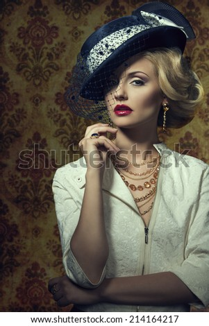 Young,blonde beautiful woman with old fashion style,  in expensive gold jewelry with smart blue hat with veil.