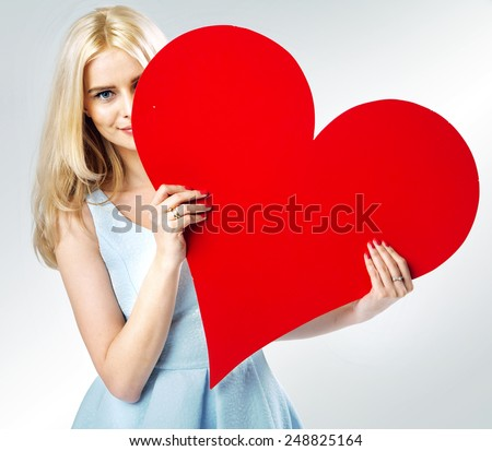 Young blonde beauty holding big heart - stock photo
