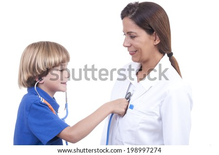 Young blonde boy wears stethoscope and listens to female physician's heart beat on white background