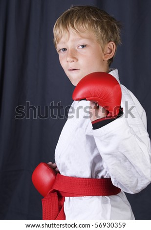 young blonde boy with his karate kit on and red belt and pads