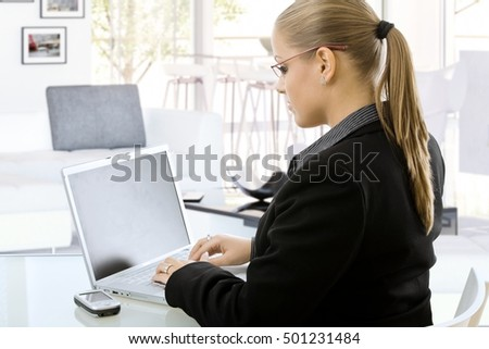 Young blonde caucasian business office worker working on laptop computer at home, sitting in front of desk, looking at screen, typing, wearing glasses.