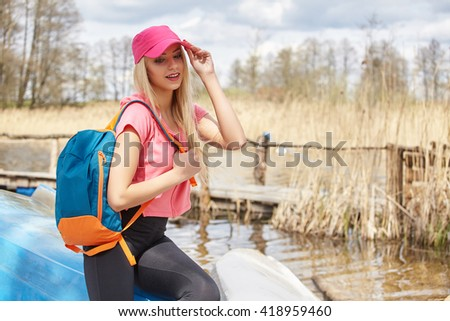 young blonde Caucasian woman hiking in nature by the lake on sunny summer day. Girl with  backpack in nature walking and relaxing.
