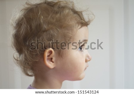 Young blonde child, girl toddler, with blonde curly hair. Taken with plain backdrop, side on. She is looking into the distance. Beautiful. Head shot. - stock photo
