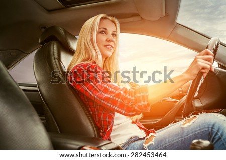 Young blonde drive a car - stock photo