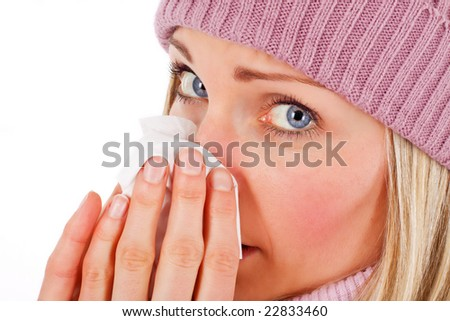 Young blonde female blowing her nose - isolated on white