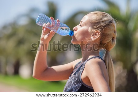 Young blonde girl drinking water during morning jogging - stock photo