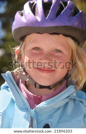 Young blonde girl in a purple bicycle helmet