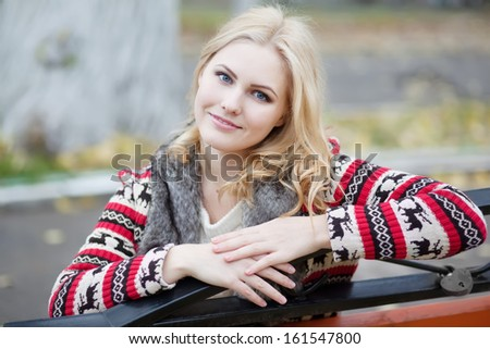 young blonde girl in cardigan with a traditional Celtic ornament - stock photo