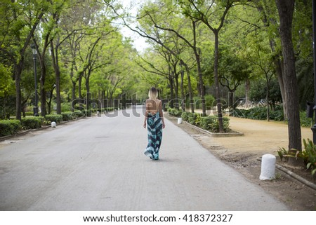 Young blonde girl in long dress walk alone in park. Outdoor