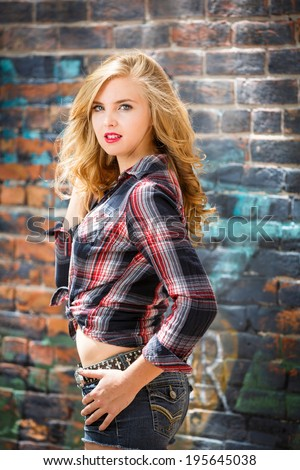 Young blonde girl in strip flannel shirt and shorts - stock photo