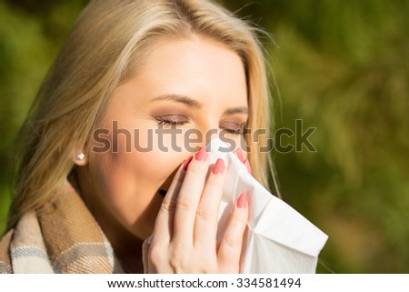 young blonde girl in the park in autumn with a tissue - stock photo