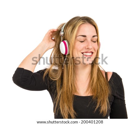 Young blonde girl listening music over white background  - stock photo