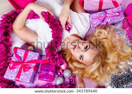 Young blonde girl lying on the couch. Around gifts and festive tinsel. Girl holding Christmas toy. New Year 2017 and Merry Christmas. Christmas tree. Angle shot from above. - stock photo