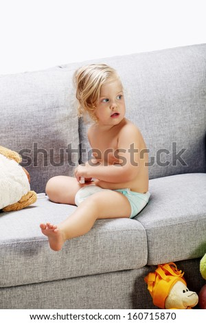 young blonde girl plays on the bad sofa in the living room - stock photo