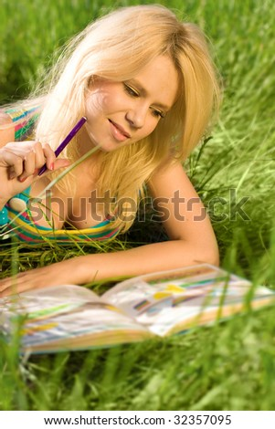 Young blonde girl reading on a lawn