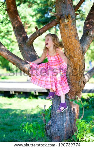 young blonde girl sitting on a tree and laughing - stock photo