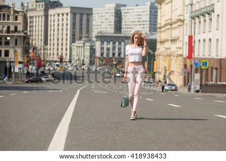 young blonde girl walks through the streets of the city. center of Moscow. Spring warm sunny day. girl dressed in pink pants and white topic