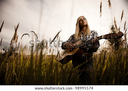 Young blonde girl with the guitar on a meadow - stock photo