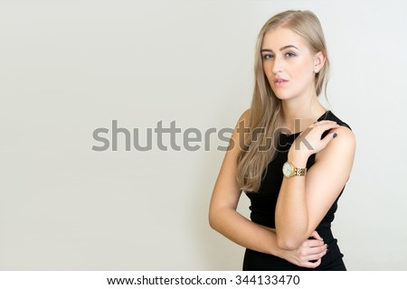 Young blonde girl woman pose black dress gold watch isolated white light background - stock photo