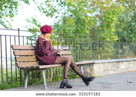 Young blonde girl writes on a tablet in the bench