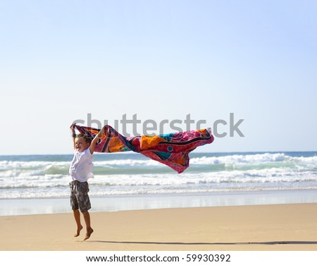 Young blonde haired boy with a sarong on the beach