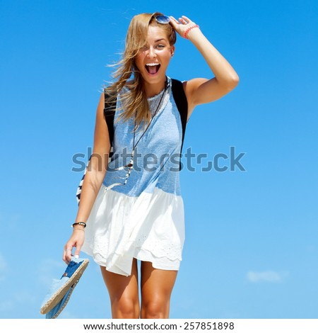 Young blonde happy beautiful tan woman have fun laughing and screaming on the beach blue sky background  - stock photo