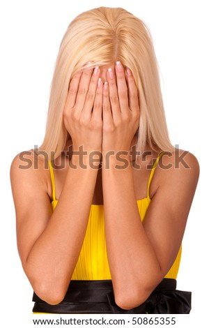 Young blonde has shut face with hands, it is isolated on white background.