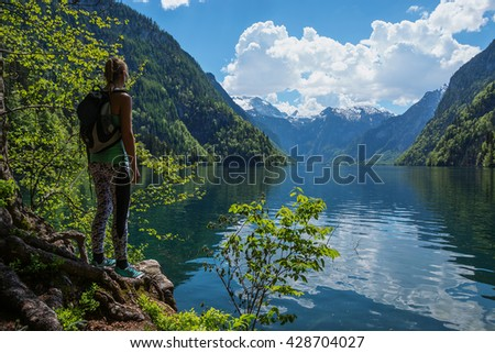 Young blonde hiking girl standing backwards at the shore of Koenigssee