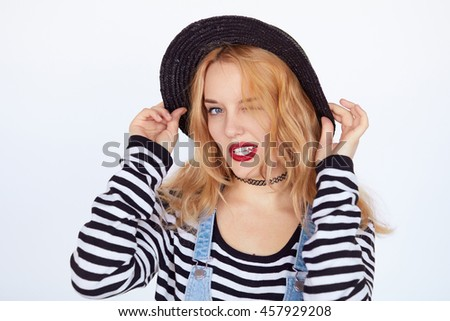 Young blonde hipster woman making funny face and posing while holding her hat over white background. Fashion teenage girl winking to camera.
