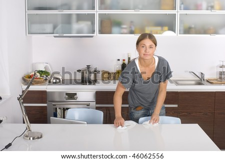 Young blonde housewife cleaning a table - stock photo