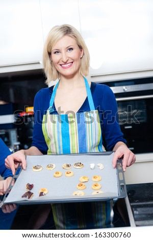 Young blonde Housewive baking Cookies - stock photo