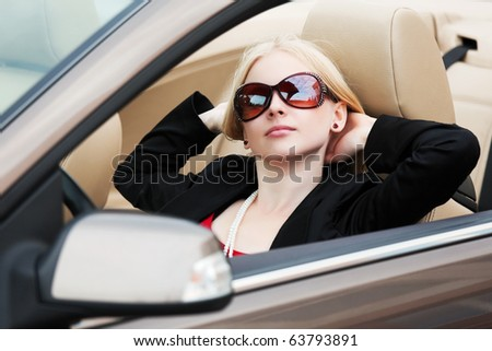 Young blonde in a convertible. - stock photo
