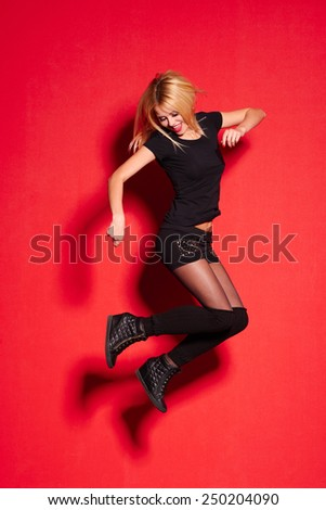 Young blonde lady in black posing on red - stock photo