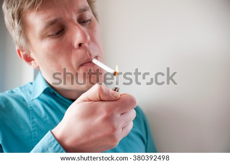 Young blonde man lighting cigarette