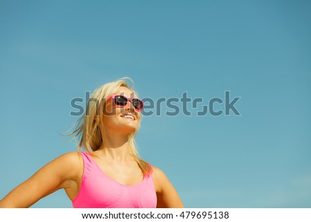 Young blonde pretty girl on beach. Woman wearing sunglasses have active time in summer. Summertime concept with copy space.