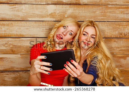 Young blonde sisters make fun group selfie, holding a tablet computer. A girl shows tongue. The concept of youth and technology. - stock photo