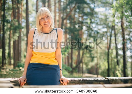 Young blonde smiling woman in cute dress outdoors.