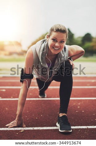 Young blonde sportswoman looking at camera while stretching on stadium before running, listening to music