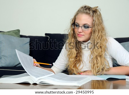 Young blonde student turning page in book
