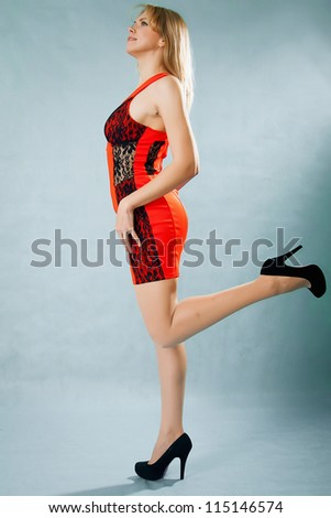 Young blonde wearing a red dress - stock photo