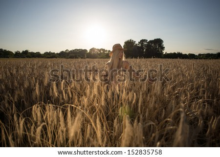 Young blonde wearing hat standing on the meadow. - stock photo