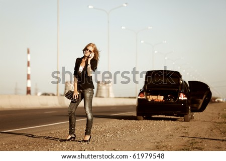 Young blonde with a broken car. - stock photo